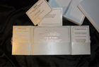 Wedding invitations silk folio with ribbon and broach and printed inserts