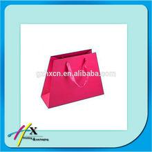 Folding rose pink paper gift bag with ribbon handles