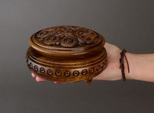 Handmade round wooden jewelry brown box with carving.