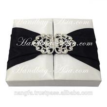 White couture invitation box featuring rhinestone lock brooch, black silk lace + gate closure