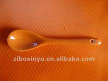 orange color ceramic spoon with hole