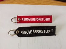 wholesale cheap remove before flight embroidered keychain manufacturers