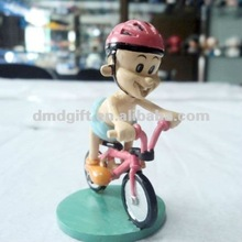Plastic action figure model riding a bike/bicycling