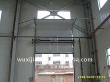 Power operated vertical overhead lift industrial sectional exterior doors