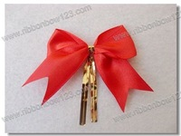 Red satin ribbon gift bow with metallic